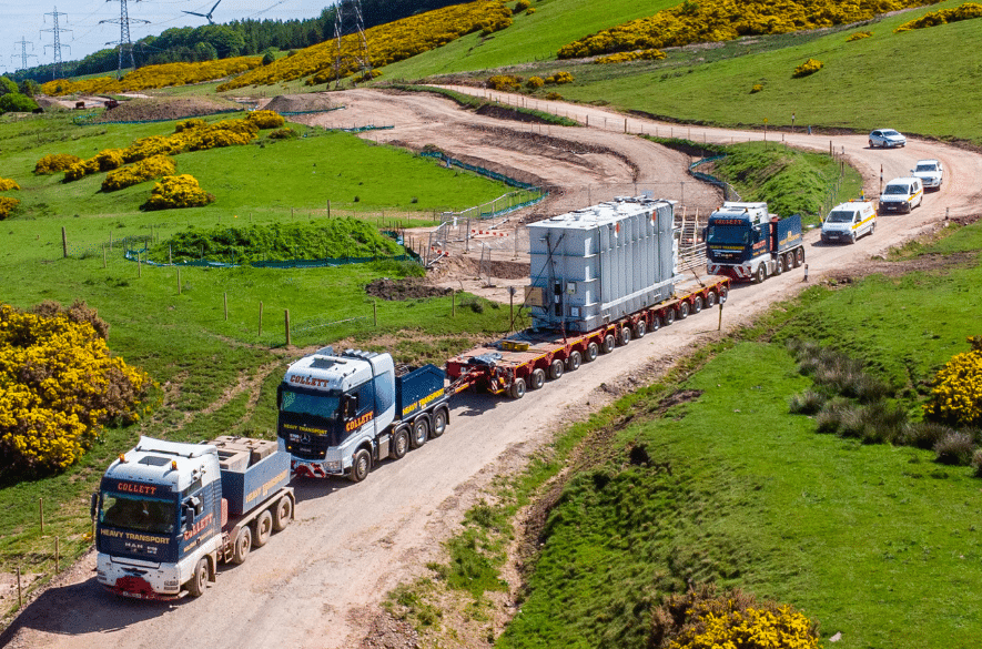 An aerial photo of a convoy with the Neart na Gaoithe shunt reactor travelling to Crystal Rig