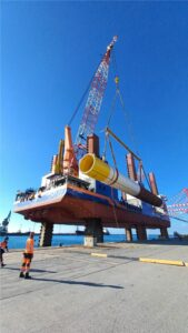 A photo of the MPI Resolution vessel loading a monopile for the Taranto offshore wind farm in Italy