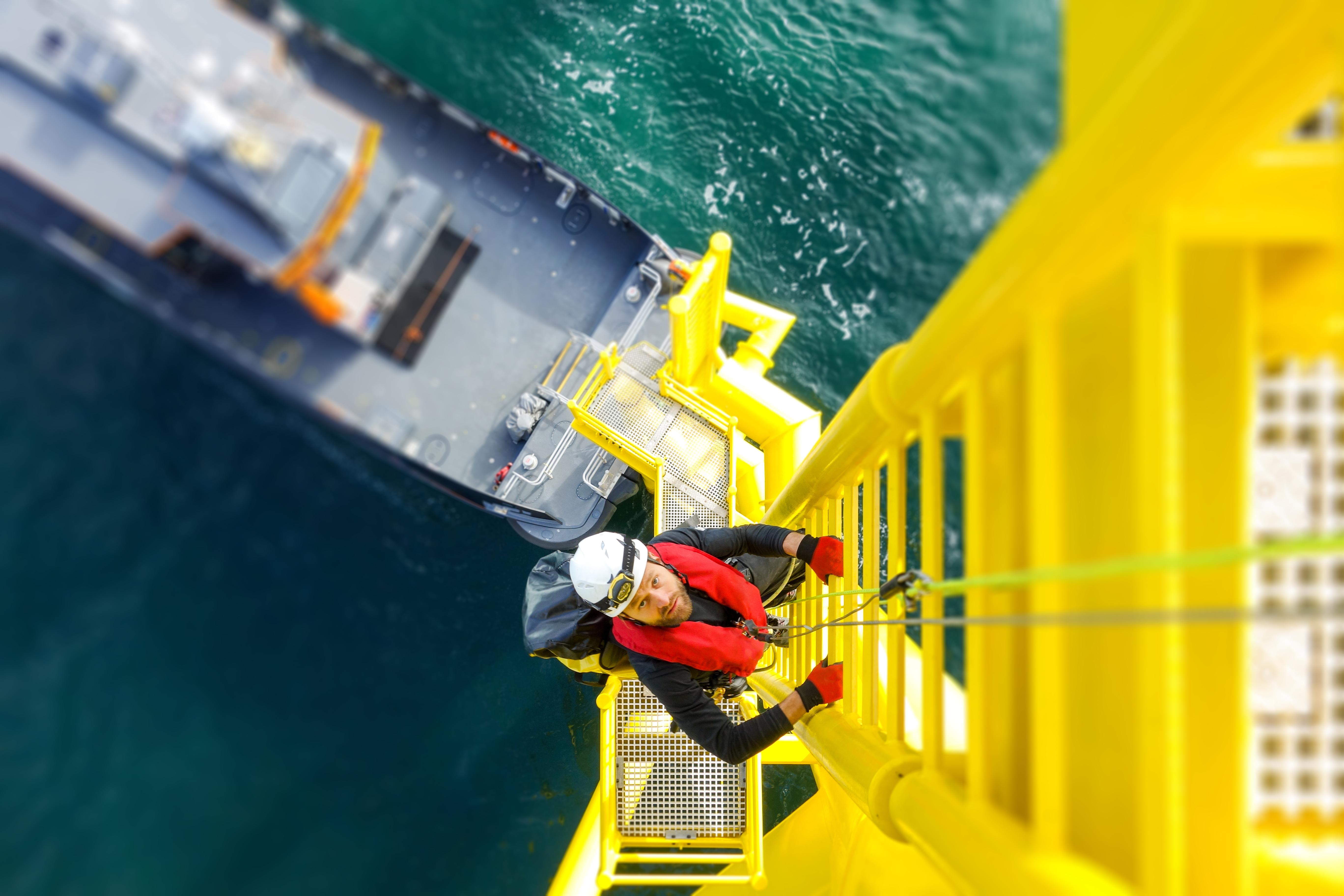 Werknemer klimt de trap op bij een offshore Windturbine.