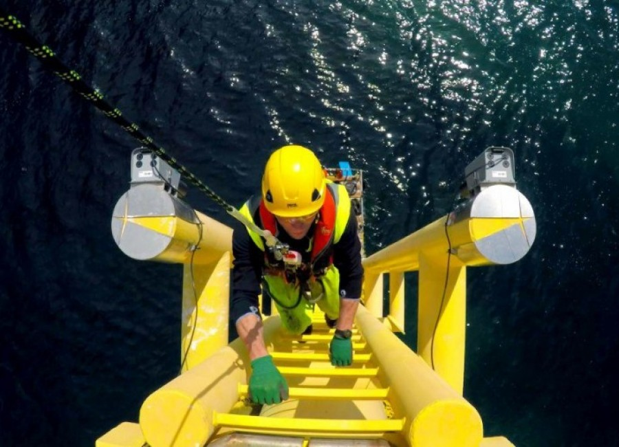 A photo taken from the top of an offshore wind turbine, showing a technician climbing up the turbine