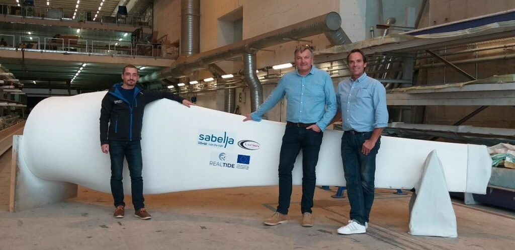 A photo of Erwann Nicolas, Fanch Le Bris, and Vincent Marsaudon beside the blade prototype (Courtesy of Sabella)