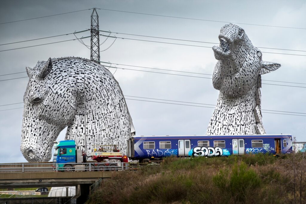 Image of Scotrail carraige loaded onto a truck, on its way to Bo-Ness, travelling past The Kelpies at Grangemouth, Forth & Clyde Canal.