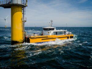 A photo of a Windcat crew transfer vessel docking onto a wind turbine
